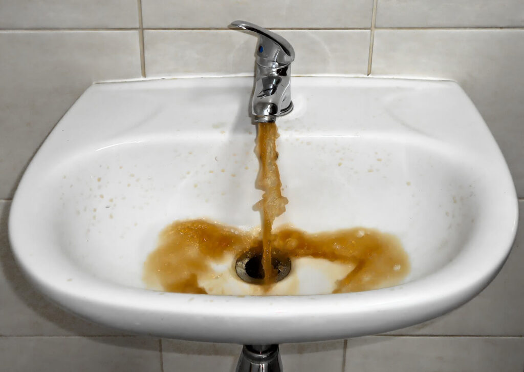 What causes yellow stains in bathtub, sink, shower, and toilet bowl